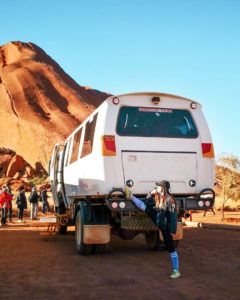 Off-road tour bus parked at the base of Uluru